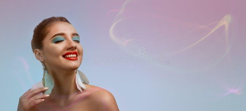 Studioskott av en ung härlig le flicka med ljus makeup och med stängda ögondrömmar av något som är angenäm mot färg royaltyfri fotografi