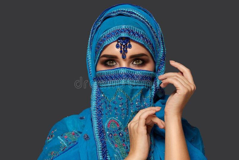 Studioskott av en ung h?rlig kvinna som b?r den bl?a hijaben som dekoreras med paljetter och smycken arabisk stil fotografering för bildbyråer