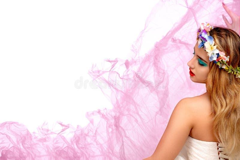 Studioskott av en ung kvinna med makeup och den blom- kransen på hennes huvud arkivfoto