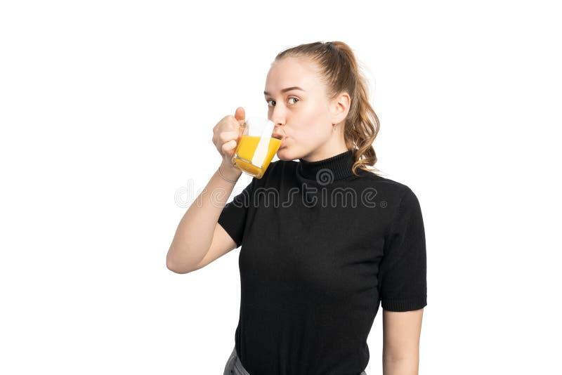 Studioskott av en ung kvinna som dricker ett exponeringsglas av orange fruktsaft arkivfoto