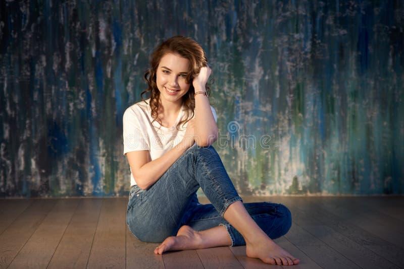 Studioskott av en ung le flicka i jeans och ettskjorta sammanträde på golvet Ljust solljus, positiva sinnesrörelser arkivfoton