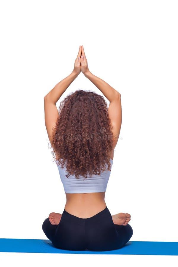 Studioskott av en ung passformkvinna som gör yoga royaltyfri fotografi