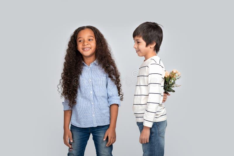 Studioskott av en ung pojke som ger blommor till en flicka som isoleras royaltyfria foton
