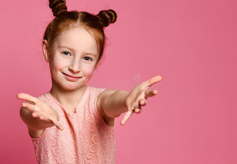 Studioskott av en vänlig gullig rödhårig manliten flicka som drar händer in mot arkivbild