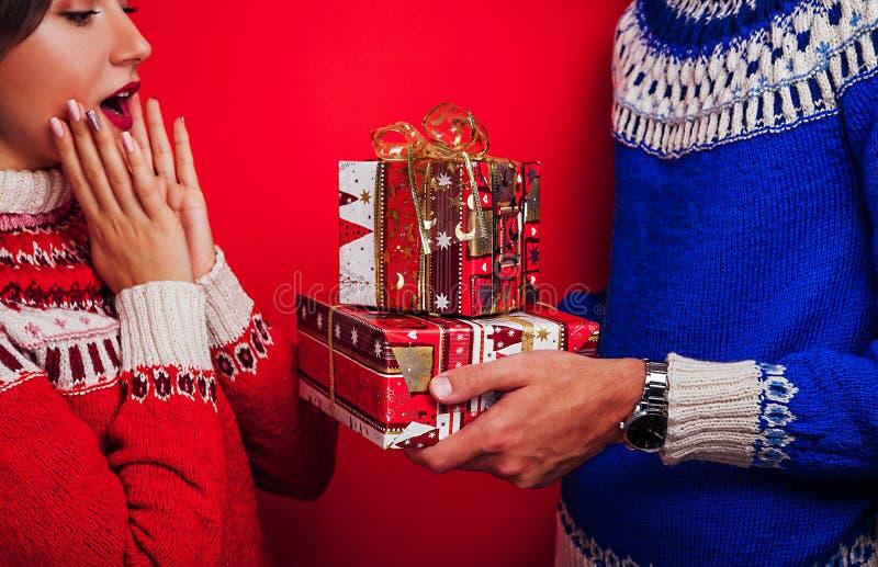 Studioskott av ett par i isländska tröjor Man som ger hans flickvän gåvaaskar Jul eller berömbegrepp för nytt år arkivfoton