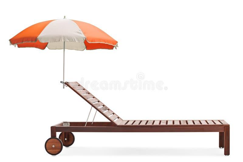 Studioskott av ett trä sunbed med ett orange och vitt paraply royaltyfria bilder