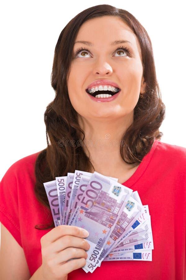Studioskott av hållande upp fläktade ut sedlar för en ung kvinna royaltyfria bilder
