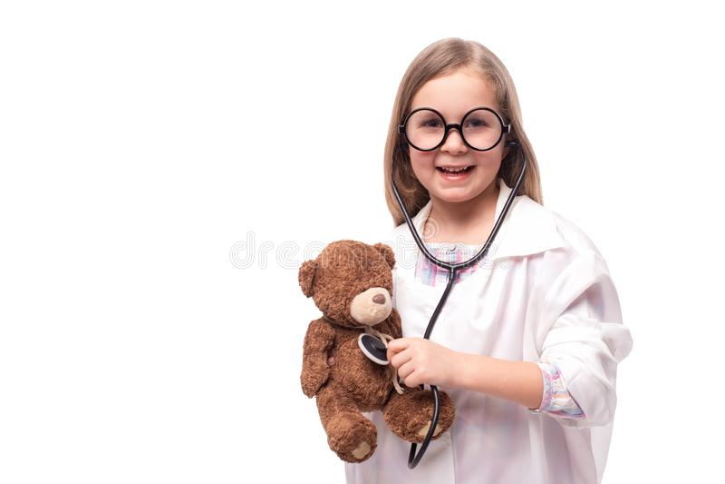 Studioskott av lite att le flickan i en vit medicinsk kappa med en stetoskop som behandlar en nallebjörn på en vit bakgrund med royaltyfri foto