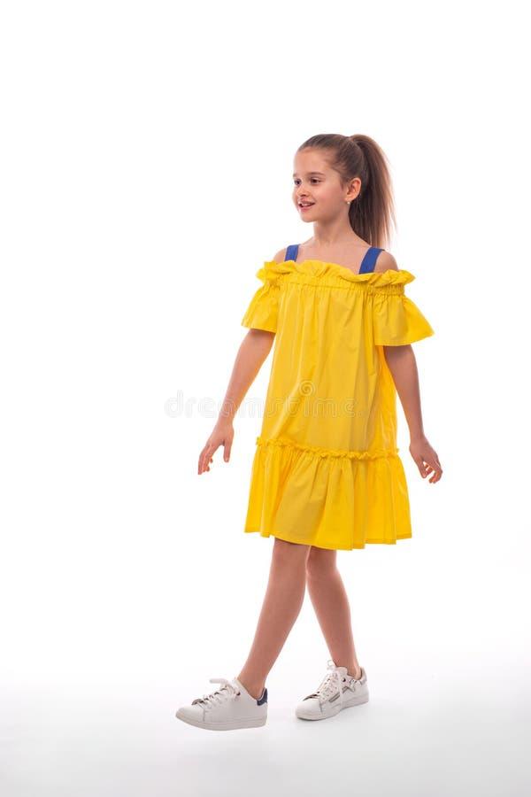 Studioskott av lite att le flickan som bär gula sundress och vita gymnastikskor på en vit bakgrund Hon går någonstans i a arkivfoto