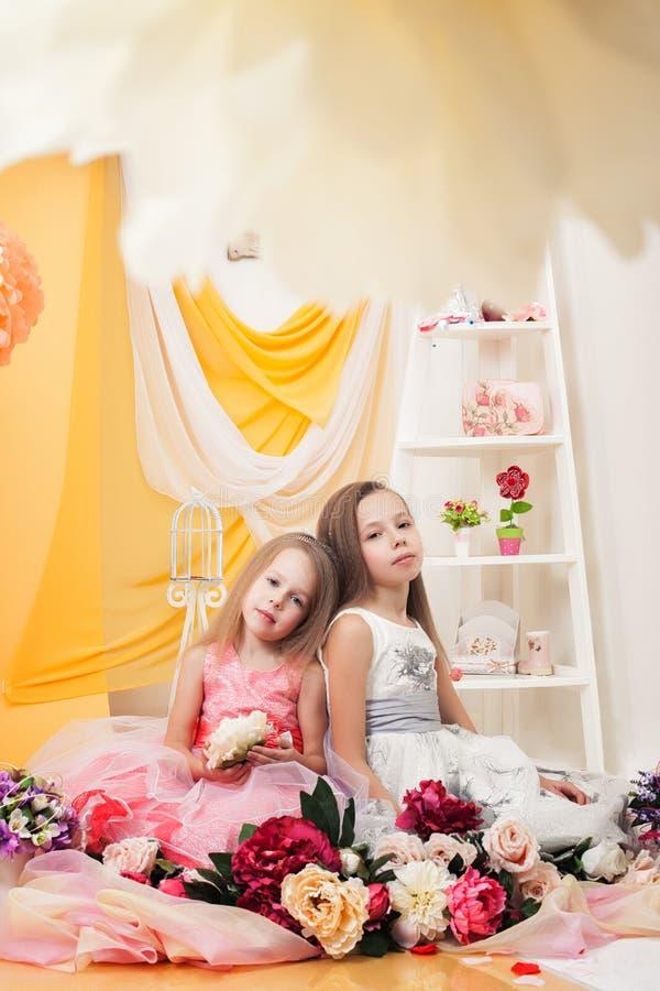 Studioskott av nätta systrar som poserar med blommor royaltyfri foto