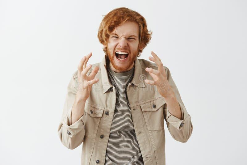 Studioskott av rödhårig manmannen under argument som skriker och gör en gest med ilsket ett uttryck som griper hårt om lyftta hän royaltyfria foton