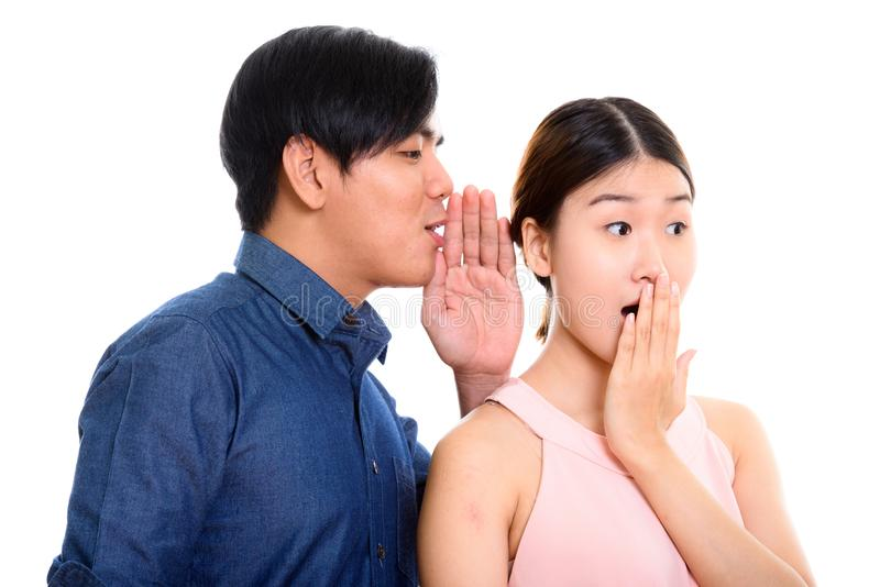 Studioskott av unga asiatiska par med mannen som viskar till kvinna l arkivfoton