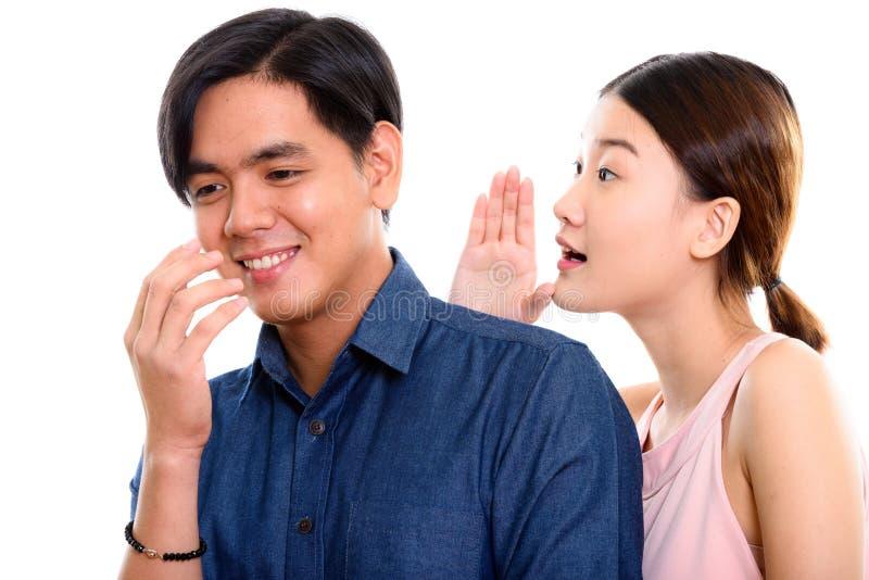 Studioskott av unga lyckliga asiatiska par som ler med kvinnawhisp royaltyfri foto
