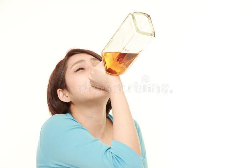 Studioskott av ungt japanskt dricka för kvinna som är rakt från en flaska arkivbild
