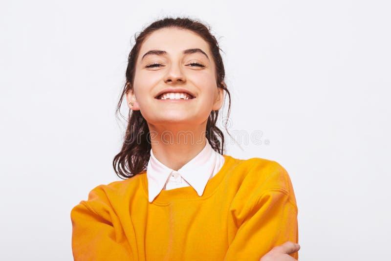 Studioskottet av att charma den unga kvinnan, ler i huvudsak, bär den orange tröjan med den vita skjortan royaltyfri foto