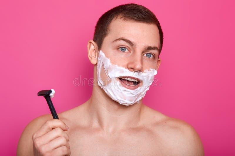 Studioskottet av den attraktiva grabben som poserar med rakkniven i badrum och att stå med kräm på framsida och öppnad mun, har f arkivbild