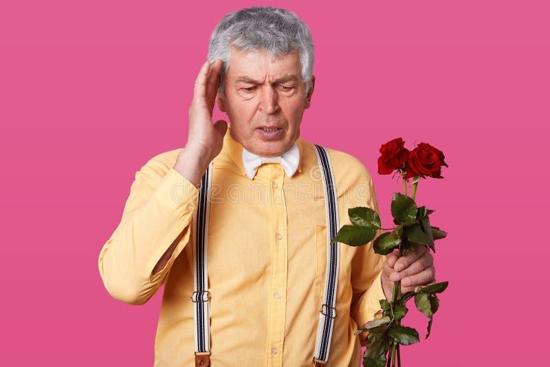 Studioskottet av den gråa haired äldre mannen i den trendiga gula skjortan, hängslen, den vita flugan, håller handen på temp royaltyfri fotografi