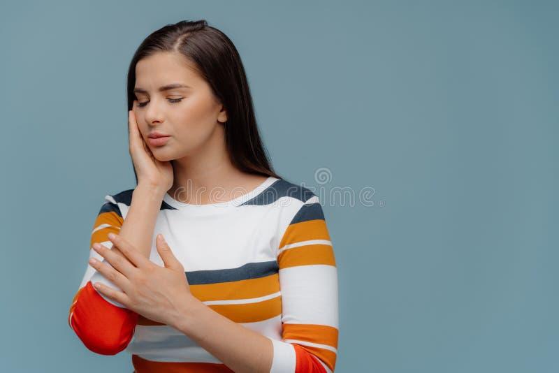 Studioskottet av den mörka haired kvinnan trycker på kinden, lider från tandvärk, har smärtsamma känslor, har ögon att stängas, b royaltyfri bild