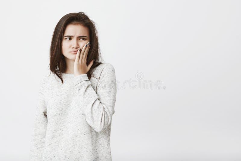 Studioskottet av den unga härliga kvinnliga modellen med brunt hår och att rymma gömma i handflatan på kinden som uttrycker dyste royaltyfri bild