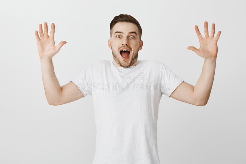 Studioskottet av den upphetsade entusiastiska stiliga mannen med att lyfta för borst gömma i handflatan höjd och att ropa från ly arkivbild