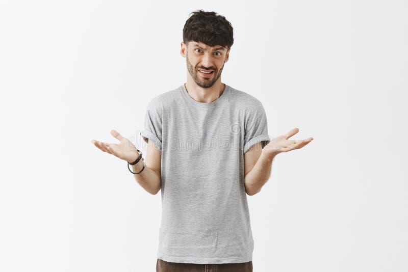 Studioskottet av mannen som förklarar något enkelt som ifrågasättas någon, kan inte förstå att rycka på axlarna med spridning göm arkivfoto