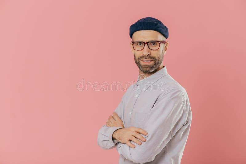 Studioskottet av själven försäkrade skäggiga mannen med blåa ögon, bär den stilfulla hatten, och den vita skjortan, håller armar  royaltyfri bild
