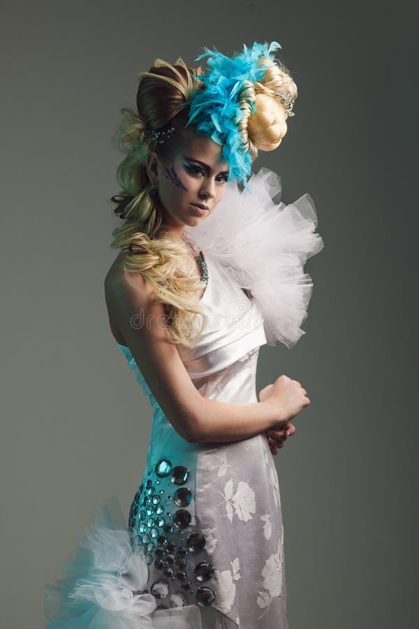 Studiospruit van vrouw met creatieve kapsel, make-up en kleding stock foto