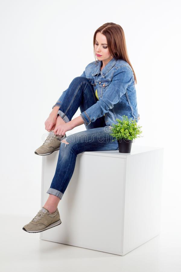 Studiostående av bärande jeans för härlig kvinna som binder hennes gymnastikskor fotografering för bildbyråer