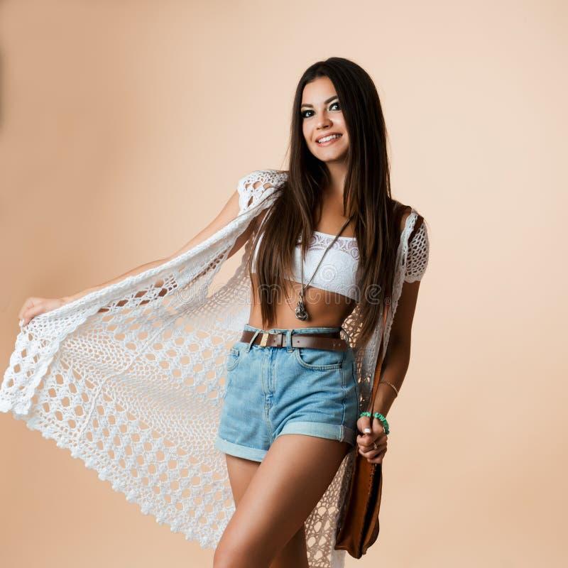 Studiostående av den emotionella stilfulla och attraktiva flickan som poserar, ler och ser kameran Stå och rymma arkivbild