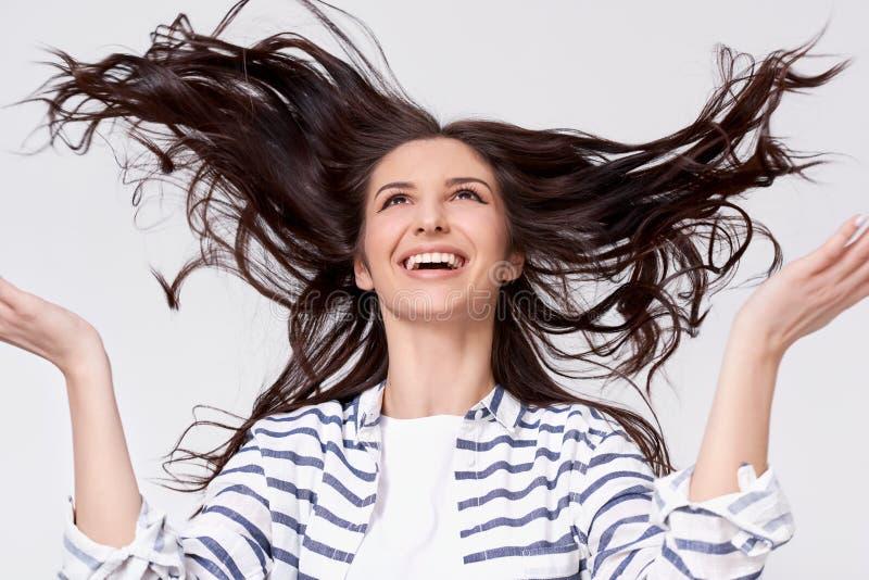 Studiostående av den härliga glade brunettkvinnan med flyghår som ler och skrattar att se upp med lyftta händer arkivbild