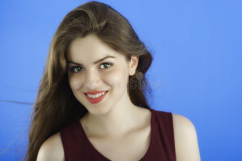Studiostående av den härliga kvinnan med långt hår på blå backgr royaltyfria bilder