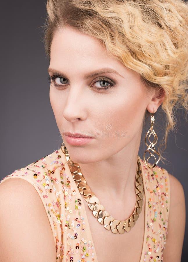 Studiostående av den härliga kvinnan med yrkesmässig makeup och guld- hår arkivbilder