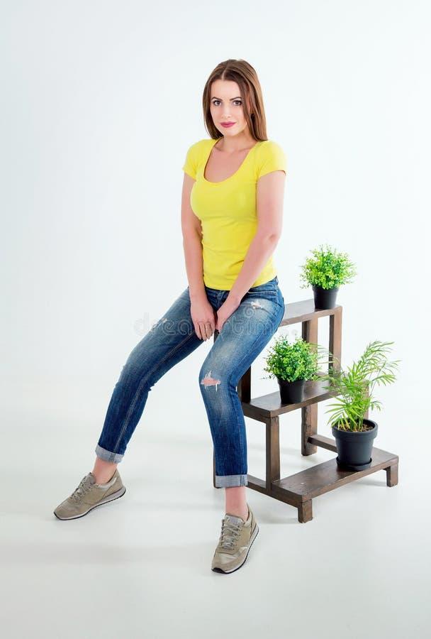 Studiostående av den härliga unga le kvinnan som sitter nära houseplants royaltyfri bild