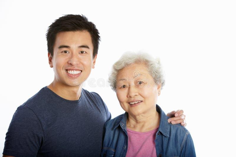Studiostående av den kinesiska modern med den vuxna sonen arkivfoto