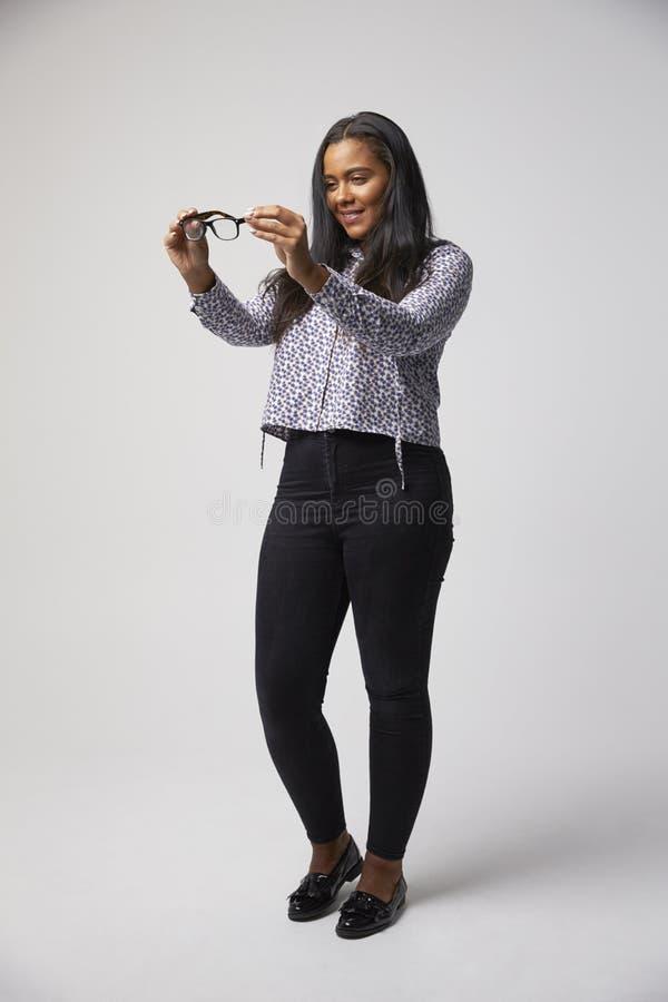 Studiostående av den kvinnliga optiker Looking At Spectacles fotografering för bildbyråer