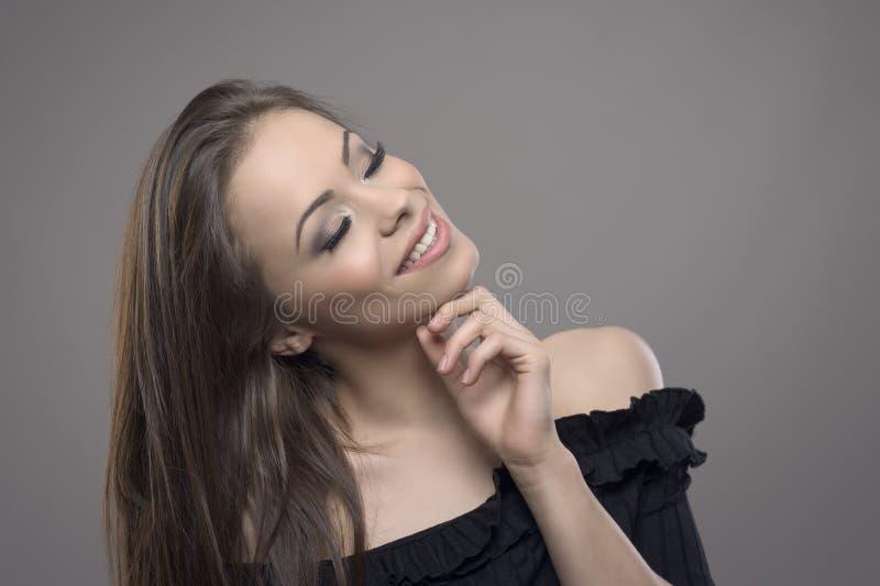Studiostående av den lyckliga härliga kvinnan som ler med den stängda ögon och handen på hakan royaltyfria bilder