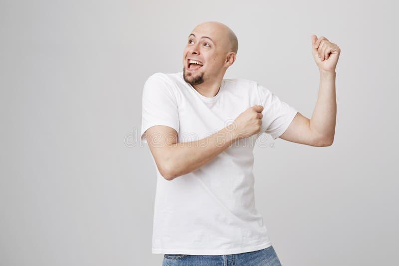 Studiostående av den realitet förkrossade skalliga caucasian mannen med skäggdans med lyftta händer som åt sidan ser och royaltyfri foto