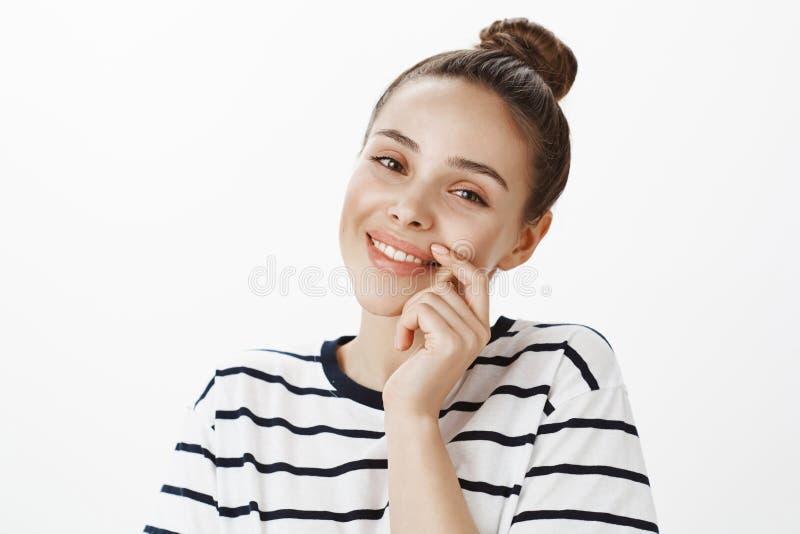 Studiostående av den säkra härliga unga europeiska kvinnan i randig t-skjorta, vippning och rörande framsida försiktigt royaltyfria bilder
