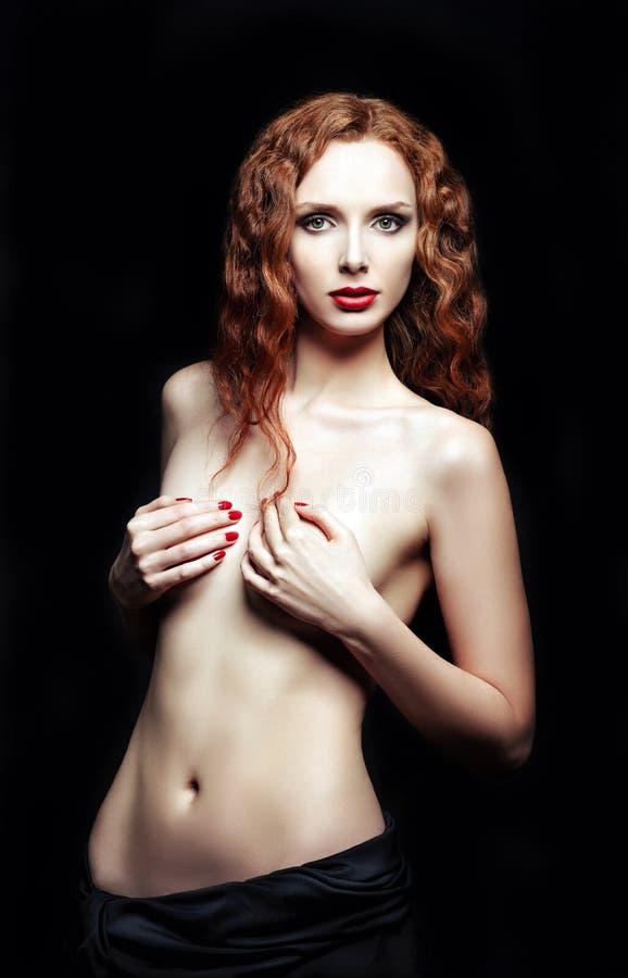 Studiostående av den sexiga rödhåriga kvinnan på svart bakgrund arkivbild