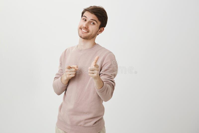Studiostående av den stiliga caucasian grabben med borstet som ler och uttrycker positiva sinnesrörelser, medan peka på kameran fotografering för bildbyråer