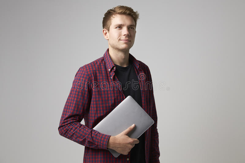 Studiostående av den tillfälligt klädda affärsmannen With Laptop arkivfoto