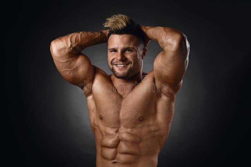 Studiostående av den topless muskulösa idrottsmannen som ler över svart royaltyfria bilder