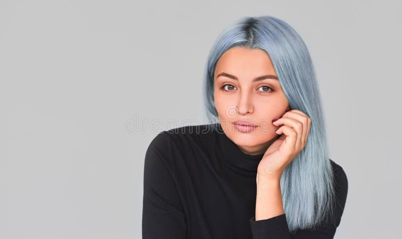 Studiostående av den unga kvinnlign med blått hår som poserar i studion som ser till kameran Iklädd svart för tonåringkvinna till arkivbilder