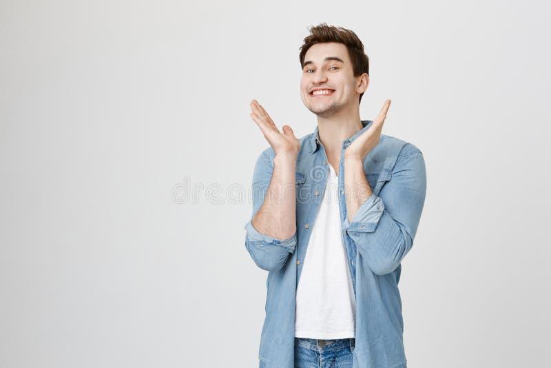 Studiostående av den unga lyckliga mannen med stilfull frisyr som glatt ler, medan lyfta händer till applåden som står royaltyfria foton
