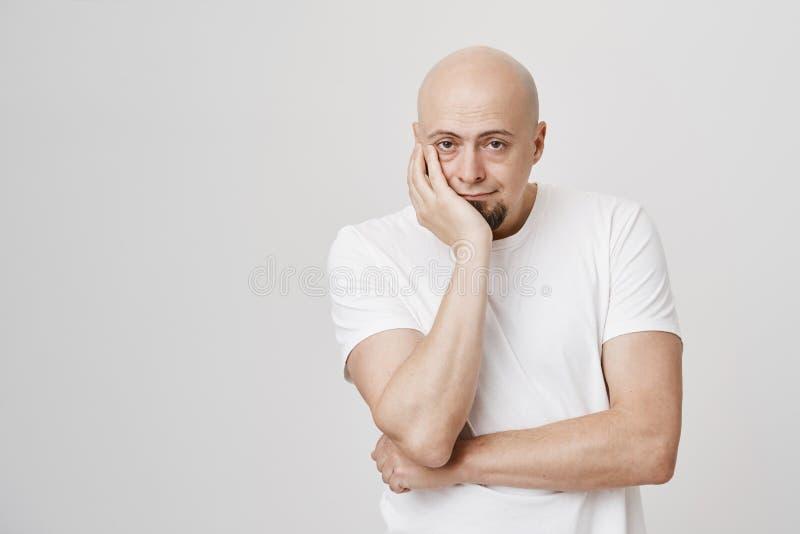 Studiostående av dyster skallig europeisk manlig modellvisningleda medan lutande huvud förestående och stå över grå färger arkivfoton