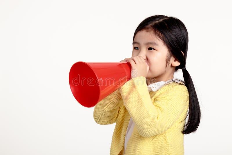 Studiostående av en asiatisk flicka som talar med en högtalare arkivfoto