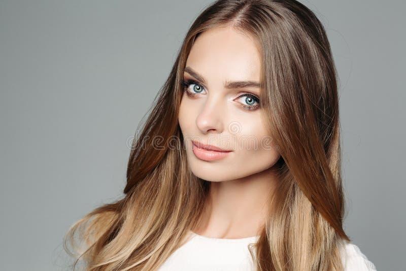 Studiostående av en attraktiv blond kvinna med lång tjock hår- och låg-tangent makeup som bär en elegant vit blus royaltyfri foto