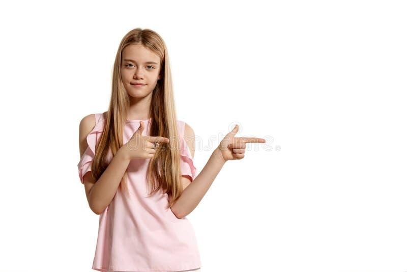 Studiostående av en blond tonåring för härlig flicka i rosa t-skjorta posera som isoleras på vit bakgrund royaltyfria foton