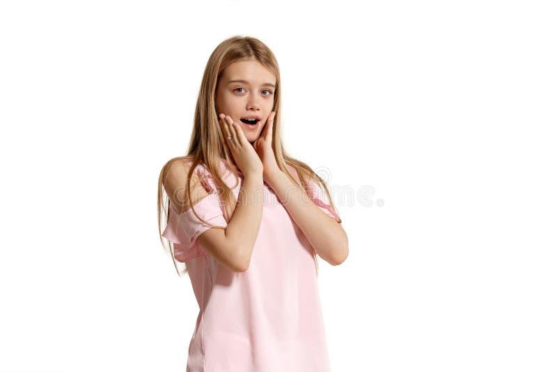 Studiostående av en blond tonåring för härlig flicka i rosa t-skjorta posera som isoleras på vit bakgrund arkivfoto