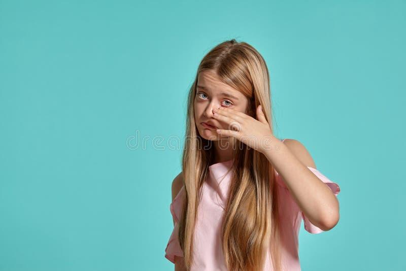 Studiostående av en blond tonåring för härlig flicka i en rosa t-skjorta som poserar över en blå bakgrund royaltyfria foton